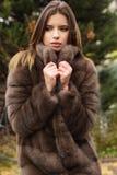 La muchacha bastante adolescente está llevando el abrigo de pieles Imagenes de archivo