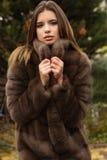 La muchacha bastante adolescente está llevando el abrigo de pieles Fotografía de archivo
