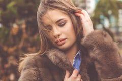 La muchacha bastante adolescente está llevando el abrigo de pieles Fotos de archivo