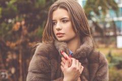 La muchacha bastante adolescente está llevando el abrigo de pieles Imagen de archivo libre de regalías