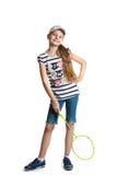 La muchacha bastante adolescente juega con una estafa para un bádminton en un fondo blanco Fotografía de archivo