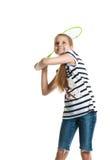La muchacha bastante adolescente juega con una estafa para un bádminton en un fondo blanco Imagen de archivo libre de regalías