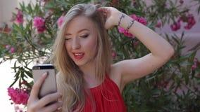 La muchacha bastante adolescente utiliza su teléfono afuera, ella presenta para un Selfie almacen de metraje de vídeo