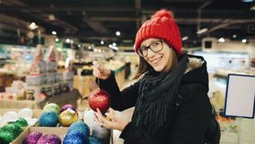 La muchacha bastante caucásica en vidrios y un sombrero rojo elige las bolas para la Navidad en el mercado y jugar con uno de metrajes