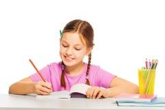 La muchacha bastante diligente en camiseta rosada aprende en la escuela Imagen de archivo libre de regalías
