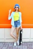 La muchacha bastante fresca de la moda con el monopatín escucha la música sobre naranja colorida Foto de archivo