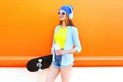 La muchacha bastante fresca de la moda con la taza de café del monopatín escucha la música sobre naranja colorida Foto de archivo
