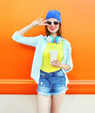 La muchacha bastante fresca de la moda con la taza de café escucha la música sobre naranja colorida Fotografía de archivo libre de regalías