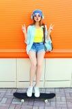 La muchacha bastante fresca de la moda escucha la música con el monopatín sobre naranja colorida Imágenes de archivo libres de regalías