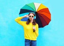 La muchacha bastante fresca de la moda escucha la música en auriculares con el paraguas colorido en día del otoño sobre fondo azu Foto de archivo