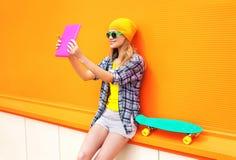 La muchacha bastante fresca de la moda hace el autorretrato en la PC de la tableta sobre colorido anaranjado Imagen de archivo libre de regalías
