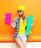 La muchacha bastante fresca de la moda hace el autorretrato en la PC de la tableta sobre naranja colorida Fotografía de archivo libre de regalías