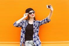 La muchacha bastante fresca de la moda hace el retrato del selfie en smartphone sobre naranja colorida Fotografía de archivo