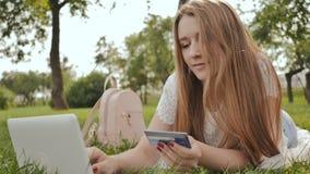 La muchacha bastante joven del estudiante hace compras en línea usando una tarjeta y un ordenador portátil de crédito almacen de video