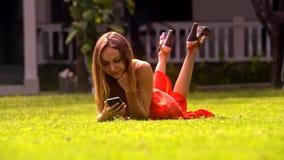 La muchacha bastante rubia miente en hierba con el teléfono en parque