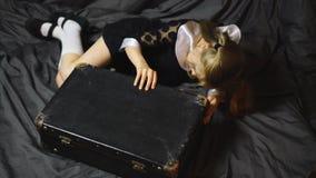 La muchacha bastante rubia mira en una maleta vieja metrajes