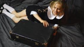 La muchacha bastante rubia mira en una maleta vieja almacen de metraje de vídeo