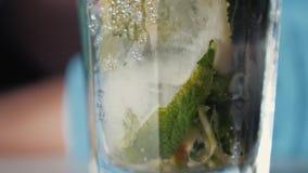 La muchacha bebe la bebida alcohólica del mojito con la menta y la cal Primer de un vidrio con mojito almacen de video