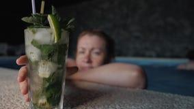 La muchacha bebe la bebida alcoh?lica del mojito con la menta y la cal Primer de un vidrio con mojito almacen de metraje de vídeo