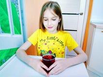 La muchacha bebe el agua con los pedazos de hielo de la fruta imágenes de archivo libres de regalías