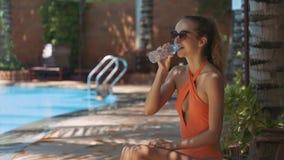 La muchacha bebe el agua de la botella en Sunny Day por la piscina