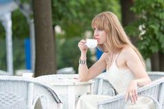 La muchacha bebe el café Imágenes de archivo libres de regalías