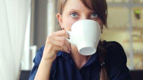 La muchacha bebe el café almacen de video
