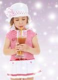 La muchacha bebe el jugo de una paja Imágenes de archivo libres de regalías