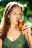 La muchacha bebe el zumo de manzana imagen de archivo