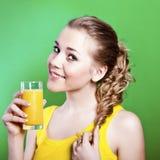 La muchacha bebe el zumo de naranja natural Imagen de archivo