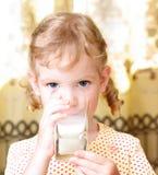 La muchacha bebe la leche Imagen de archivo libre de regalías