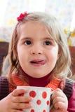 La muchacha bebe la leche Imagen de archivo
