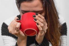 La muchacha bebe té de una taza roja grande foto de archivo