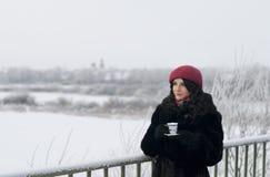 La muchacha bebe té en una mañana del invierno Imagen de archivo