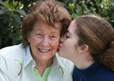 La muchacha besa a la abuela Imagen de archivo libre de regalías