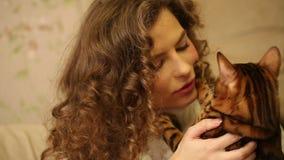 La muchacha besa su gato de Bengala almacen de video