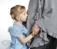 La muchacha besa un estómago de la mujer embarazada Imagenes de archivo
