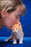 La muchacha besa un gatito rojo Foto de archivo libre de regalías