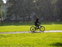 La muchacha bikes en parque urbano con lluvia y sol foto de archivo
