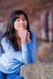 La muchacha biracial adolescente joven que descansa reservado codos en roca a lo largo del lago apuntala Imagen de archivo libre de regalías