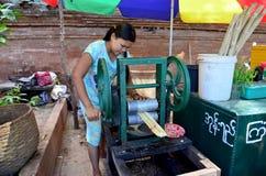 La muchacha birmana hizo el zumo de caña del azúcar por la máquina manual del fabricante para el viajero de la venta Foto de archivo