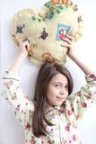 La muchacha blanca cariñosa en pijamas y el corazón juegan la almohada Foto de archivo libre de regalías
