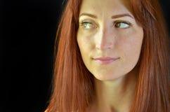 La muchacha blanca con el pelo rojo y los ojos verdes con extensiones de la pestaña en un fondo negro parece astuto derecha imágenes de archivo libres de regalías