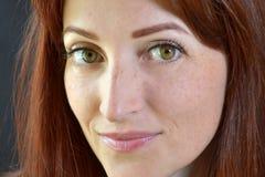 La muchacha blanca con el pelo rojo y los ojos verdes con extensiones de la pestaña en un fondo oscuro parece divertida y emocion foto de archivo libre de regalías