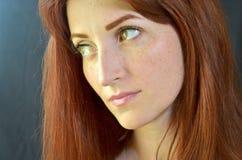 La muchacha blanca con el pelo rojo y los ojos verdes con extensiones de la pestaña en un fondo oscuro parece seriamente derecha  imágenes de archivo libres de regalías