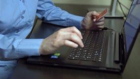 La muchacha blanca hace compras por la tarjeta de crédito vía Internet almacen de metraje de vídeo