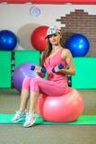La muchacha blanca hermosa joven en casquillo y traje rosado de los deportes hace ejercicios físicos con los dumbells y la bola d Imagen de archivo libre de regalías
