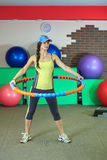 La muchacha blanca hermosa joven en un traje amarillo y gris de los deportes hace ejercicios físicos con un aro en el centro de a Imagen de archivo