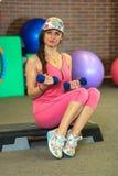 La muchacha blanca hermosa joven en un traje rosado de los deportes hace ejercicios físicos con pesas de gimnasia en el centro de Imágenes de archivo libres de regalías