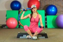 La muchacha blanca hermosa joven en un traje rosado de los deportes hace ejercicios físicos con pesas de gimnasia en el centro de Foto de archivo libre de regalías